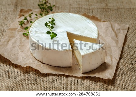 Camembert gourmet round cheese traditional French delicious dairy creamy meal  with thyme on rustic parchment and vintage sacking. Natural light, rustic style. - stock photo