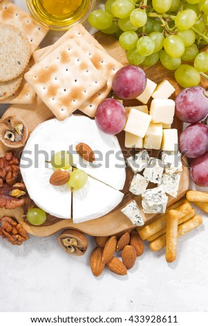 camembert, grapes and snacks on a white background, top view, closeup