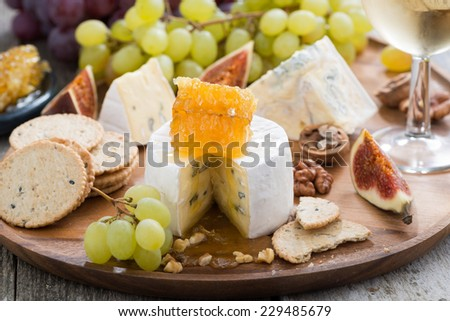 camembert with honey and fruit, snacks on a wooden tray, close-up - stock photo