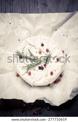 Camembert with pepper and Rosemary on wooden bacground - stock photo