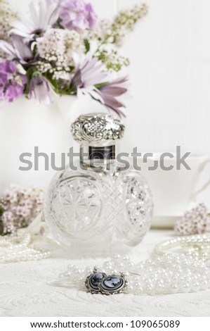 Cameo earrings on ladies dressing table with antique scent bottle in background - stock photo