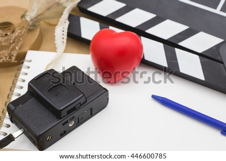 camera and clapboard on white sketchbook to represent the process to produce cinema or movie maker