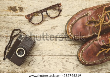 Camera and glasses and Leather shoe on a wooden , Still life travel on wooden , look vintage