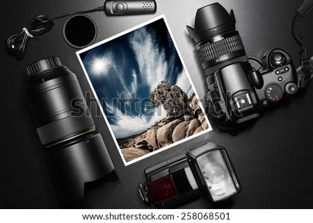 Camera equipment around a printed photo of a granite rock - stock photo