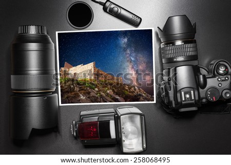 Camera equipment around a printed photo of a night sky with minky way - stock photo