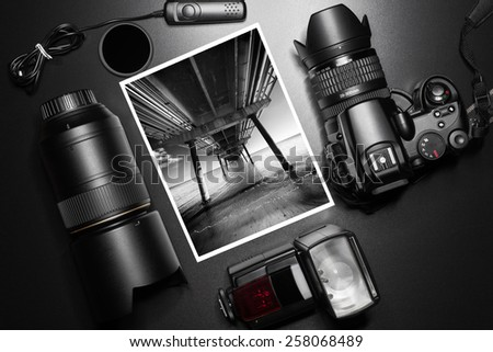 Camera equipment around a printed photo of a pier perspective - stock photo