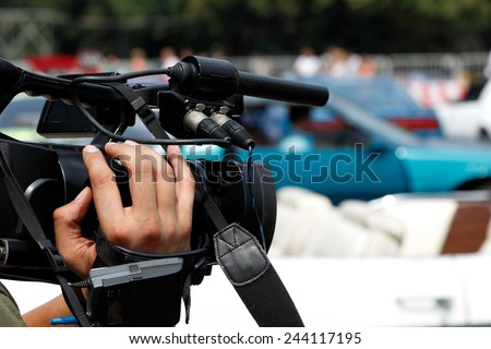 Camera in a hand of news reporter - stock photo