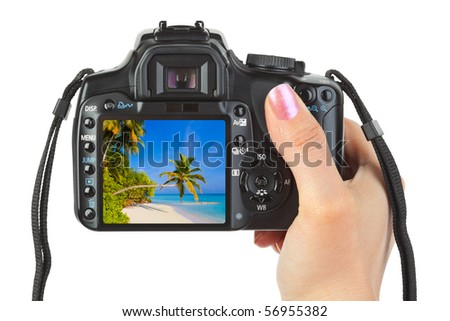 Camera in hand and beach landscape (my photo) isolated on white background - stock photo