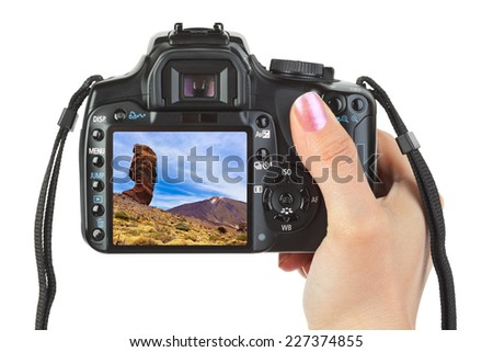 Camera in hand and Tenerife Canary view (my photo) isolated on white background - stock photo