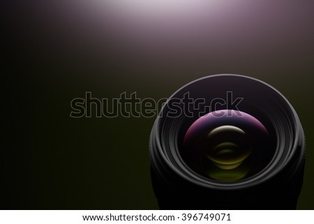 Camera lens close up on dark background - stock photo