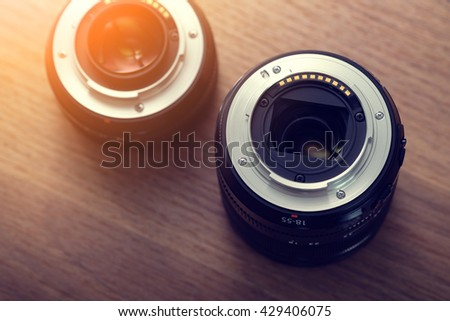 Camera lens on wooden table. - stock photo