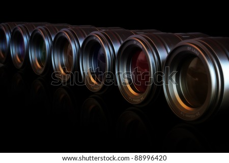 Camera lenses in a row with different color lenses with reflection. - stock photo