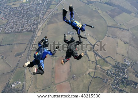 Camera man filming to skydivers - stock photo