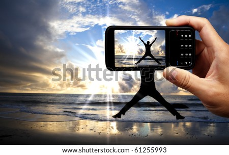 Camera mobile phone and happy jumping man on the beach at beautiful sunrise - stock photo