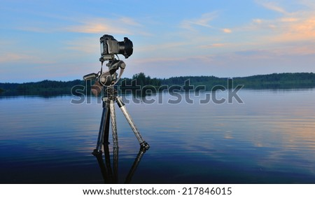 Camera on a tripod standing in water.Filming Nature.Sunset on the lake. - stock photo