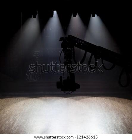 Camera on crane in empty dark hall - stock photo