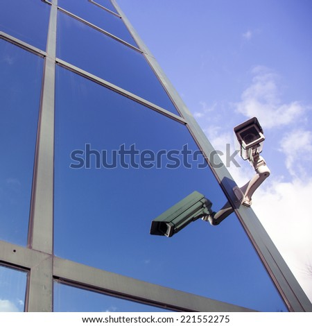 camera on glass facade of office building reflecting clouds and blue sky - stock photo
