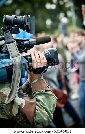 Camera operator on reportage recording crowd - stock photo