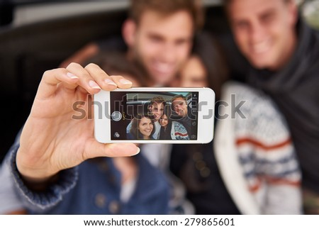 Camera phone showing face recognition blocks around the faces on the screen while a group of friends pose for a selfie - stock photo