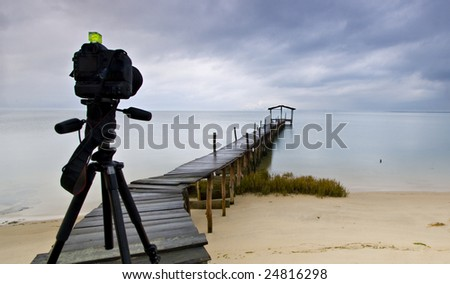 Camera standing on tripod ready to photograph a peer over the beach with shelter on a cloudy day - stock photo