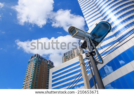 Camera system guarding blue skyscraper office building with sky above - stock photo