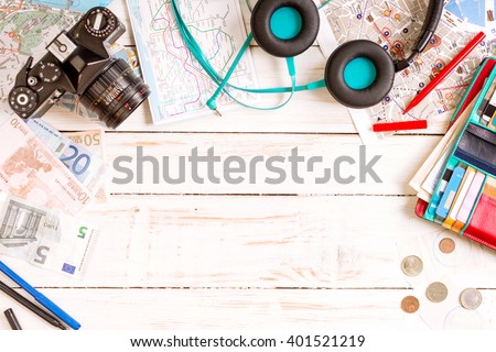 Camera, touristic maps, headphones, wallet with credit cards, phone, colorful pens, euro banknotes and coins on the white desk. Travel background. Journey planning. Tourist essentials. Space for text - stock photo