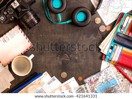 Camera, touristic maps, passport, cup of coffee, headphones, wallet with credit cards, euro banknotes and coins on the black desk. Travel background. Tourist essentials. Plan a journey. Space for text - stock photo