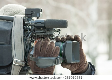 Cameraman at work outside in winter - stock photo