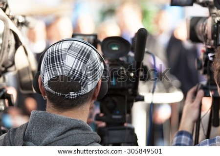 Cameraman. News conference. Filming an event with a video camera. - stock photo