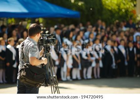 Cameraman over blurry background, primary school event graduation. - stock photo