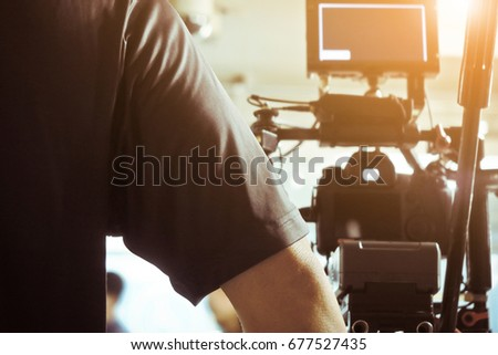 Cameraman with his video camera shooting, Adjusting Camera,film production crew. behind the scenes background.