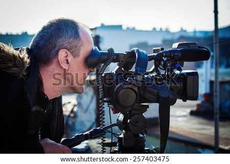 cameraman with his video camera shooting outdoor in the city on roofs - stock photo
