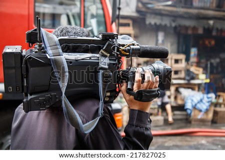 Cameraman working in the street - stock photo