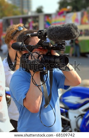 Cameraman working on the street - stock photo