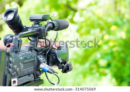 Cameraman working on tree background - stock photo