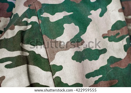 Camouflage fabric texture background. Soft selective focus and shallow depth of field - stock photo
