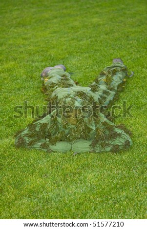 Camouflage man on the green background - stock photo