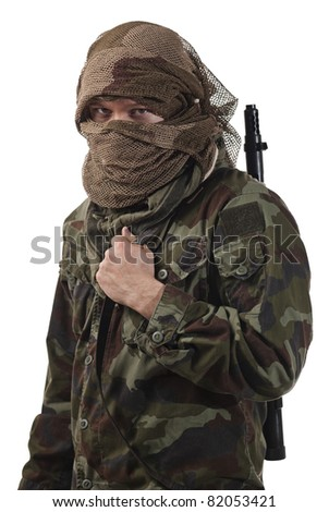 Camouflaged guerrilla soldier with hidden face and a machine gun - stock photo