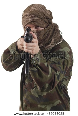 Camouflaged guerrilla soldier with hidden face and a machine gun aiming at camera. - stock photo