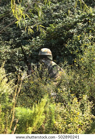 Camouflaged hunter in jungle like area with sniper rifle , He must blend into surrounding to not be detected