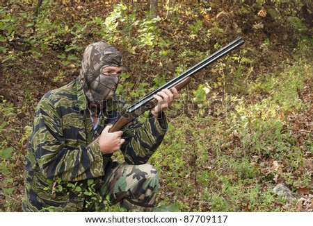 camouflaged hunter with a rifle kneeling in the woods