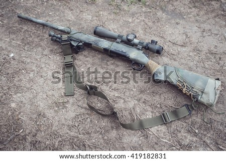 Camouflaged sniper rifle with spotting scope and equipment. Photo edited into warfare look and dust atmosphere.  - stock photo