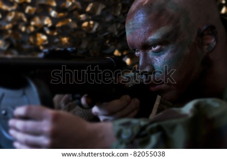 Camouflaged soldier aiming from ambush. - stock photo
