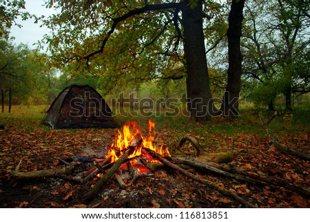 Camp fire and tourist tent in the background - stock photo
