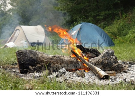 Camp Fire and two tents in the background - stock photo