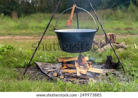 Camp fire outdoors burning with logs and pot - stock photo