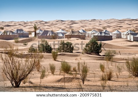 Camp of tents in a beautiful landscape of sand dunes in the desert of Sahara, South Tunisia - stock photo