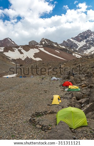 Camp on Rocky Moraine. Many camping tents assembled on Rocky Slope High Mountain Range with Peaks Snow Glacier Ice Blue Sky Clouds Background - stock photo
