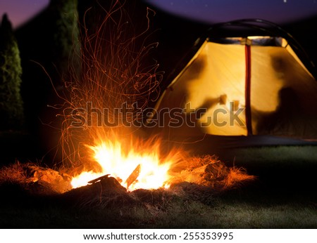 Camp shines at night. The campfire in the front as the symbol of adventure and romantic. - stock photo
