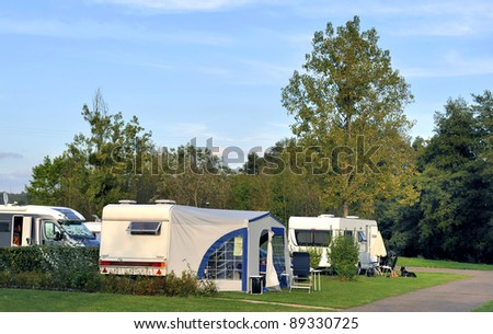 Camper and caravans at a camping at sunset. No brands, no numberplate and no people.